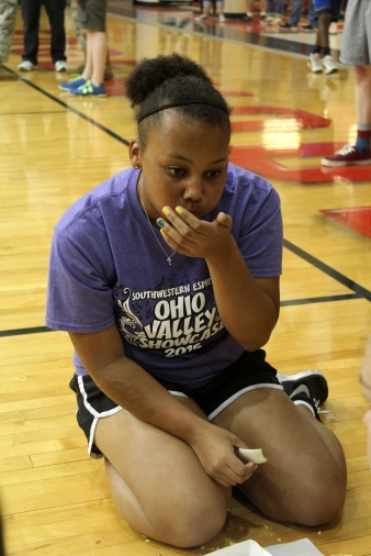 Freshman Teannah Kolbe eats a quarter of an onion during the food relay.
